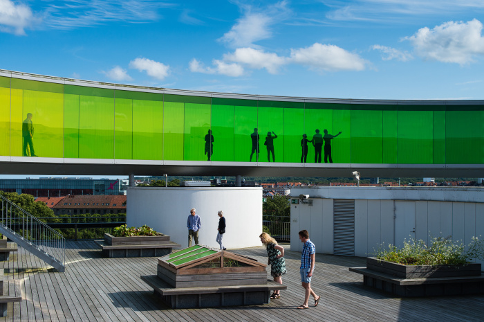 Visitors explore the roof of ARoS Aarhus Kunstmuseum and Olafur Eliasson's Your Rainbow Panorama © Rudy Mareel - Shutterstock Images